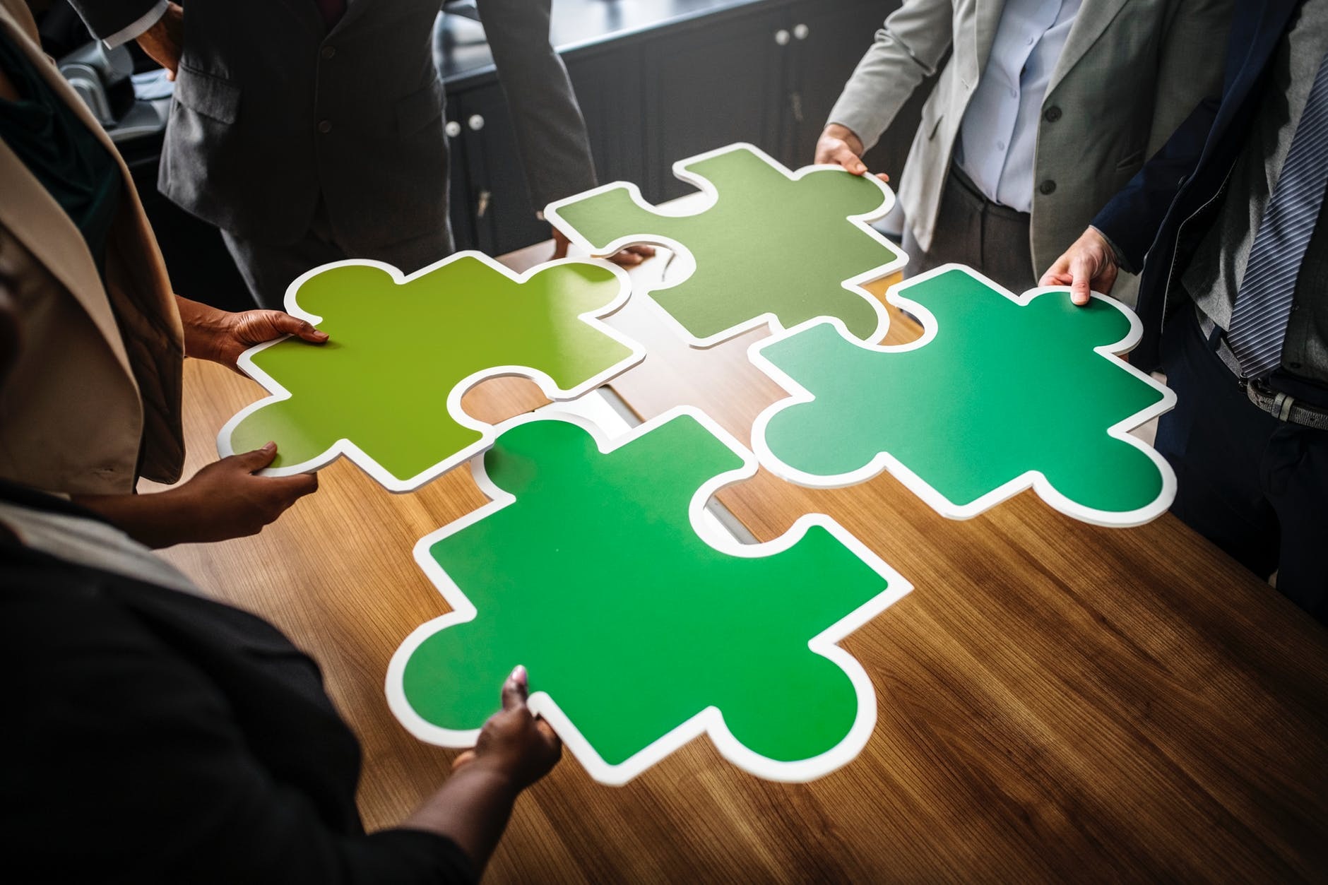 four people holding four jigsaw pieces on top of brown wooden table